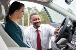 care salesman with customer showing car