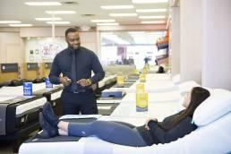 staff member explaining mattress highlights to a customer in mattress store